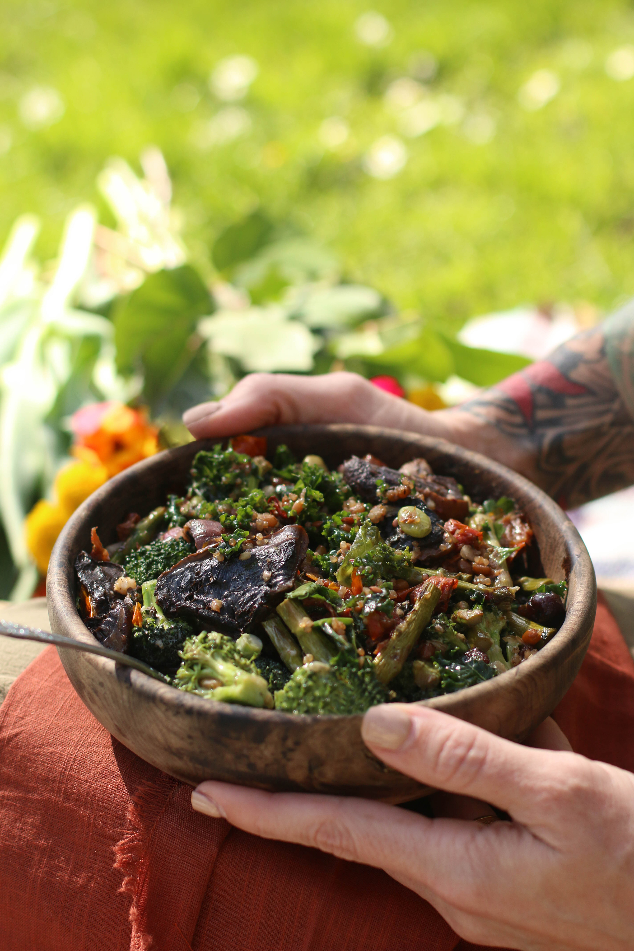 hands-holding-wooden-bowl-of-fresh-spring-greens-and-mushrooms-sitting-outdoors