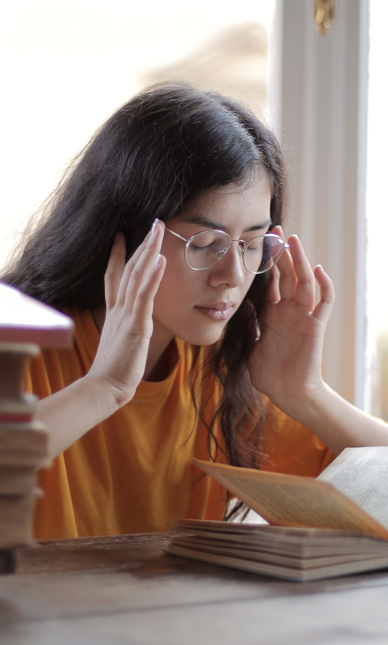young-woman-wearing-glasses-surrounded-by-books-with-eyes-closed-and-hands-on-her-temples-appearing-to-have-a-headache