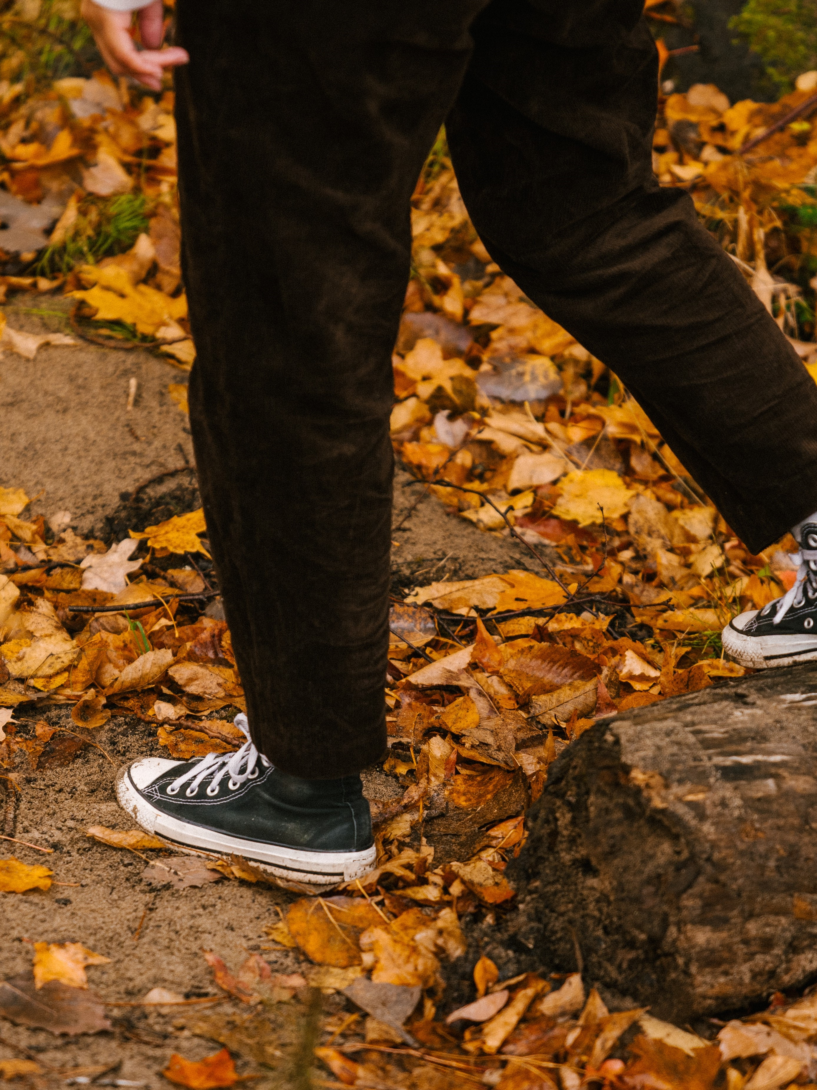 person-in-high-top-sneakers-walking-outside-over-autumn-leaves