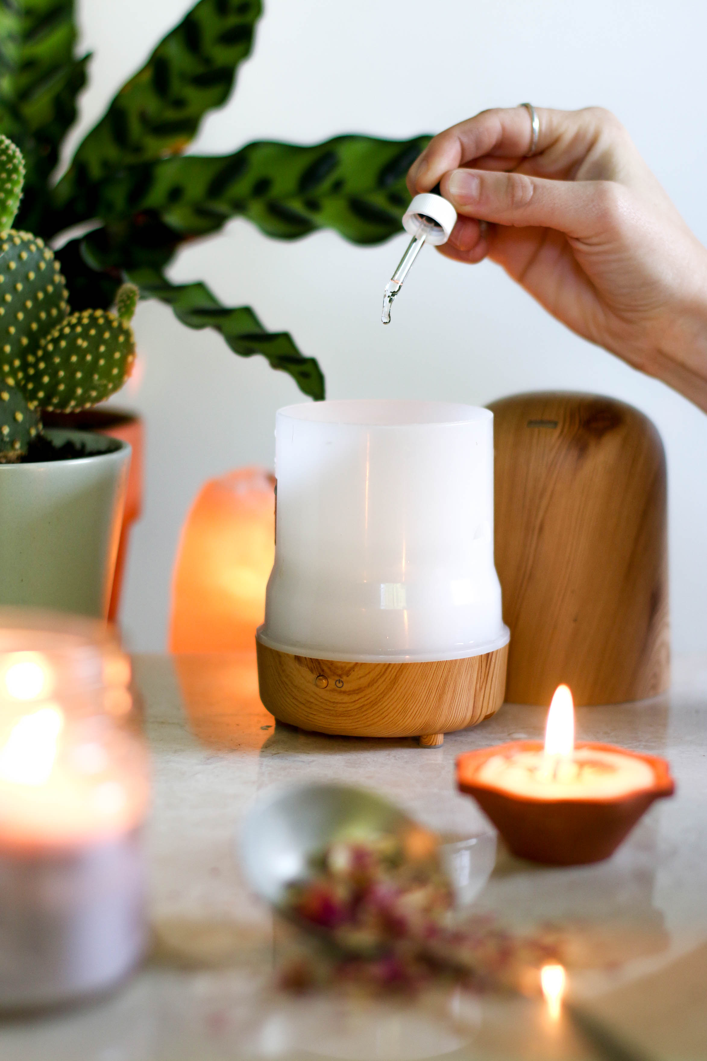 Hand-dropping-oil-into-essential-oil-diffuser-with-candles-and-plants
