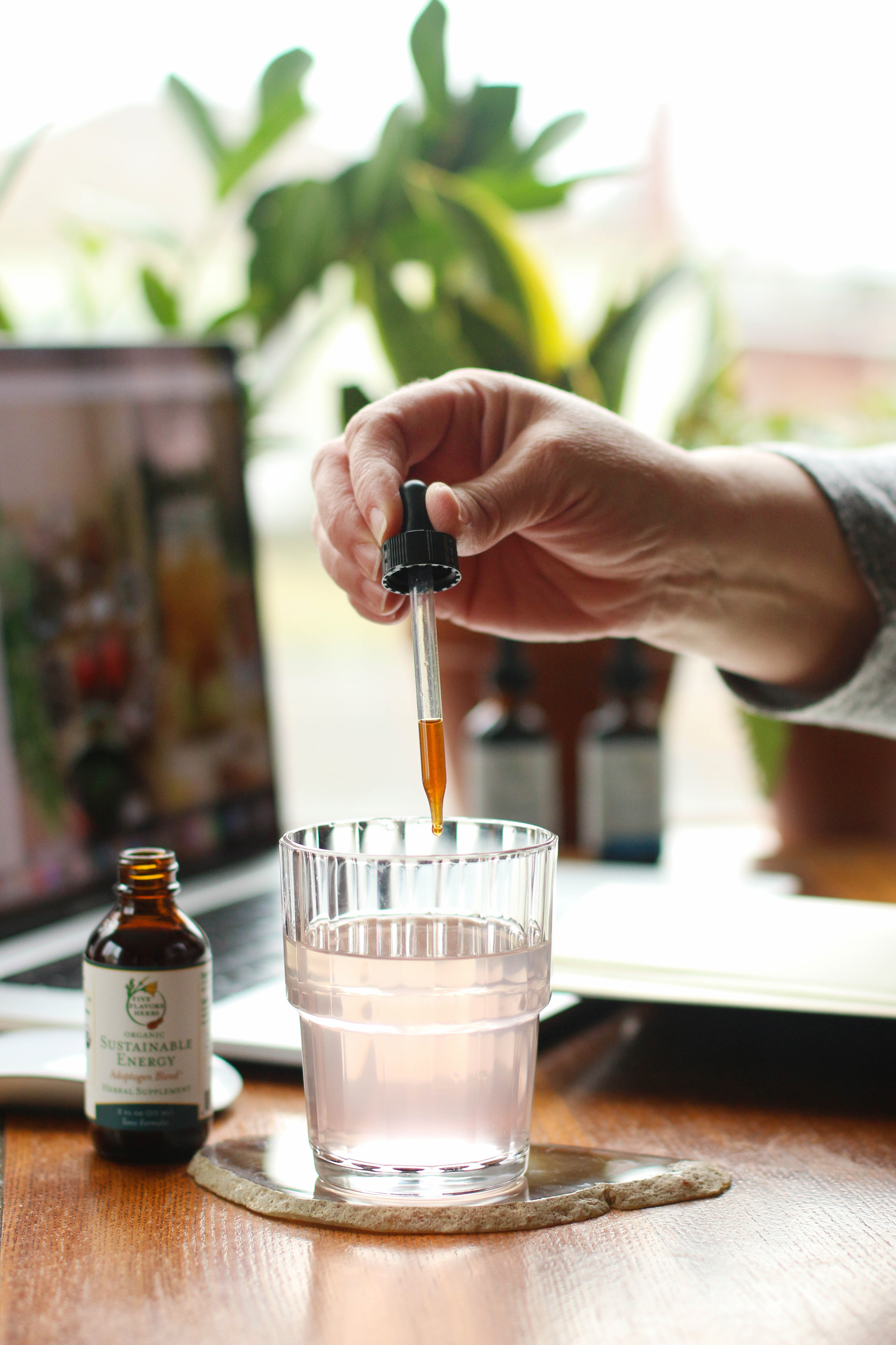 hand-holding-glass-dropper-cap-dropping-tincture-into-glass-of-water-with-work-from-home-desk-setup-in-background